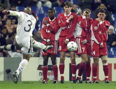 Real Madrid's Brasilian Roberto Carlos (L) shoots a ball towards a wall of Russian Spartak Moscow players (From R to L) Ilia Tsymbalar, Vasili Baranov Leandro Samarone and Robson December 9 during early action of their European Champions league sixth Group C soccer match.  DB/AA