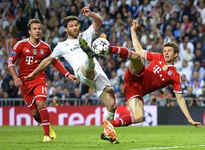 Real Madrid's midfielder Xabi Alonso (C) vies with Bayern Munich's midfielder Mario Goetze (L) and Bayern Munich's midfielder Thomas Mueller during the UEFA Champions League semifinal first leg football match Real Madrid CF vs FC Bayern Munchen at the Santiago Bernabeu stadium in Madrid on April 23, 2014. Real Madrid won the match 1-0.   AFP PHOTO / GERARD JULIEN